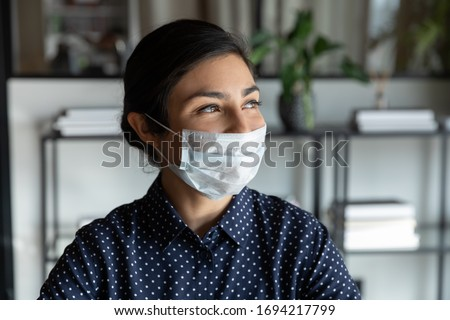 Happy young indian female company manager in protective mask looking away lost in thoughts, head shot close up. Positive smiling mixed race businesswoman dreaming of future, planning weekend time. #1694217799
