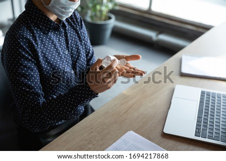 Close up above view responsible cautious young indian female employee in medical mask sanitizing hands with alcohol-based antiseptic liquid, keeping doing safety hygienic routine against coronavirus. #1694217868