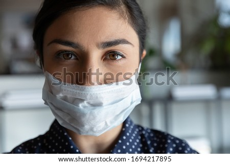Close up head shot portrait young serious cautious indian ethnic woman employee worker wearing protective medical mask, looking at camera, keeping corporate quarantine rules, healthcare concept. #1694217895