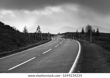 a monochrome image of a winding road cutting through the amazing Scottish Highlands. The moody atmosphere of the clouds inspired the black and white conversion adding more drama to the scene.
