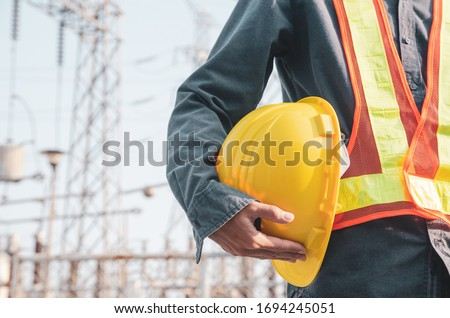 Yellow safety helmet is in the hands of an electrician. Royalty-Free Stock Photo #1694245051