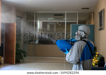 Coronavirus Pandemic. Disinfecting of office to prevent COVID-19, worker in hazmat suit with disinfect in office. #1694282296
