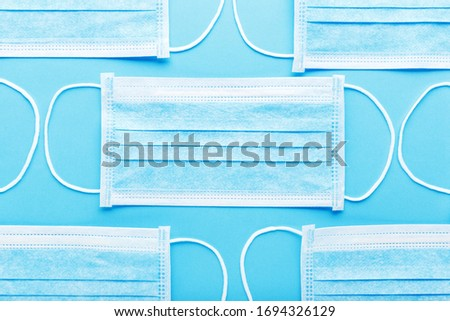 Medical hygienic mask, Face protective masks on blue background.Disposable surgical face mask protective Coronovirus Covid-19,pollution, virus, flu.Healthcare medical surgical Flat lay pattern #1694326129