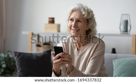 Dreamy happy hoary mature elderly woman holding smartphone, feeling positive about received message. Smiling pleasant middle aged grandma looking outside, thinking of future meeting or dating at home. #1694337832