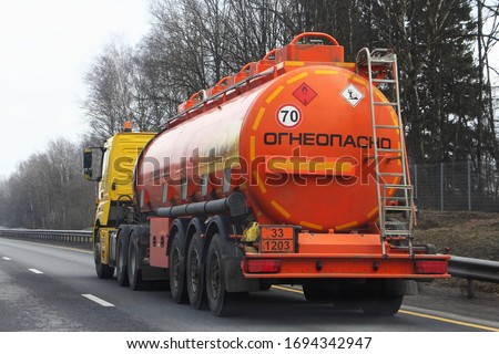 Modern bright orange semi truck fuel tanker with 33 1203 dangerous class sign and Russian inscription FLAMMABLE drive on highway at spring day in perspective, rear side view - ADR hazardous cargo Royalty-Free Stock Photo #1694342947
