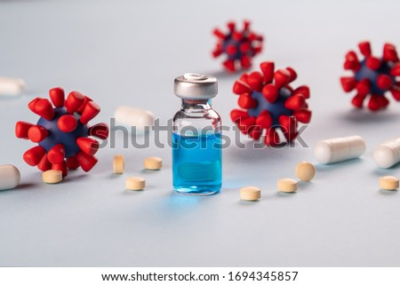 COVID-19,Coronavirus concept. Medication for treatment and prevention of new corona virus infection,  and models of covid-19 virus on blue background. Royalty-Free Stock Photo #1694345857