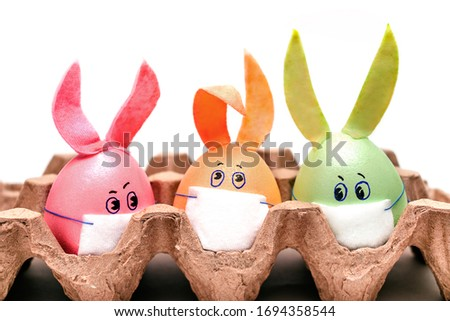 Three multicolored Easter eggs with painted eyes, rabbit ears and protective masks are in an egg container. Coronavirus epidemic concept. Concept celebrating Easter in self-isolation and quarantine #1694358544