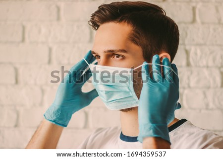 Confident young surgeon doctor in latex protective gloves wearing medical mask on face. Man professional medic in medical gloves put on protective face mask. Personal protection. Coronavirus COVID-19 #1694359537