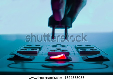 Hand plugging in extension sockets while switch power was on. Close up of hand inserting electric plug in extension sockets Royalty-Free Stock Photo #1694363086