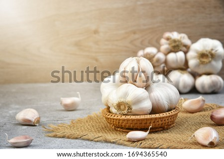 Organic Garlic. Fresh Garlic Cloves and Garlic bulb in wooden basket on dark background with Pile of garlic or spice. Selected focus. Concept of spices for healthy cooking. #1694365540