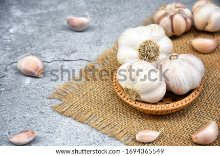 Organic Garlic. Fresh Garlic Cloves and Garlic bulb in wooden basket on dark background with Pile of garlic or spice. Selected focus. Concept of spices for healthy cooking. #1694365549