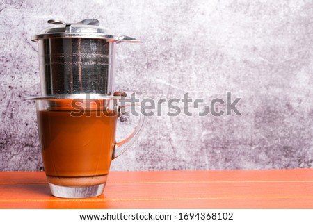 A picture of homemade Vietnamese coffee or cafe da on wooden table and copy space crack wall. #1694368102