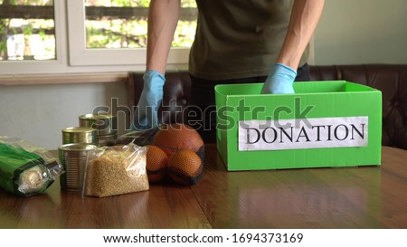 Coronavirus Relief Funds and Donations. Volunteer in the Protective Medical Mask and hand Gloves Putting Food In Donation Box. Charity donations. Making Donations To Food Bank Royalty-Free Stock Photo #1694373169