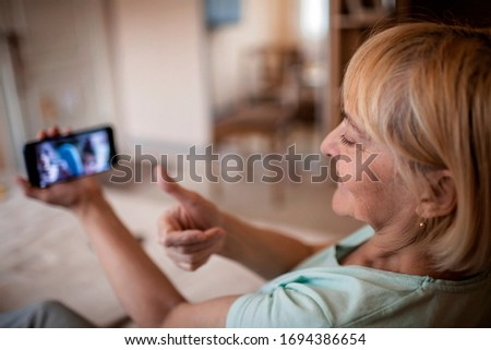 A senior woman talking with her grandchild within video chat via smartphone, digital conversation, life in quarantine time, self-isolation Royalty-Free Stock Photo #1694386654