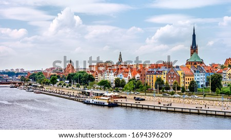 Ships anchored on Odra River pier. People relaxing on Piastowski Boulevard. Cathedral Basilica of St James the Apostle in background, Szczecin, Poland Royalty-Free Stock Photo #1694396209