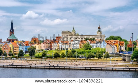 People walking on Piastowski Boulevard. Old town, Castle of Pomeranian Dukes and Cathedral Basilica of St James the Apostle in background, Szczecin Royalty-Free Stock Photo #1694396221