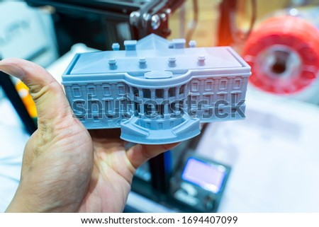 hand with builds a house closeup object printed 3d printer close-up. Progressive modern additive technology 4.0 industrial revolution #1694407099