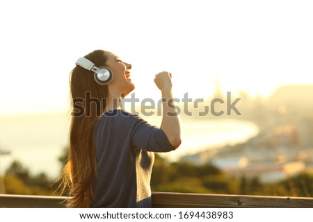 Happy girl singing listening music on headphones in a park at sunset #1694438983
