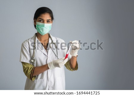 Woman Doctor holding a test tube with blood sample for coronavirus or 2019-nCoV analyzing. #1694441725