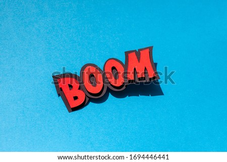 Handmade paper speech bubble on blue background. Cartoon and pop art style. Boom text. Expression.