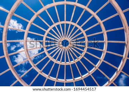 Top of large white radial canopy, with a little rust, for weddings in a public garden under a blue sky with a few light clouds, for themes of weather, radial symmetry, interconnection