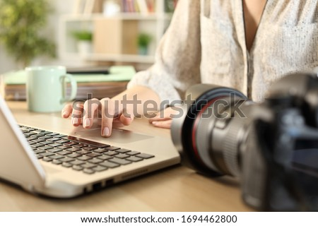 Close up of photographer woman hands connecting camera and laptop transfering files on a desk at home