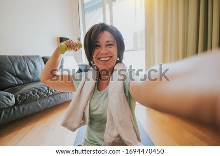 Happy mature woman taking a selfie at workout gym at home during quarantine. Concept about people, gym at home, sport. #1694470450