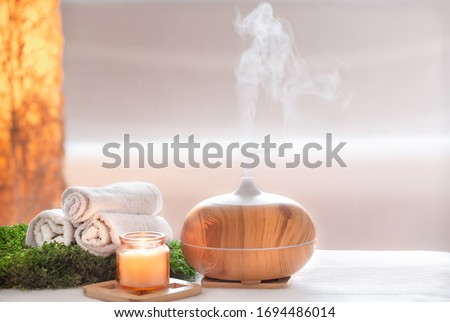 Spa composition with the aroma of a modern oil diffuser with body care products . Twisted white towels, spring greens and flowers. Spa concept for body and health care . Royalty-Free Stock Photo #1694486014