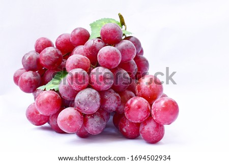 Red grape, large fresh grape fruit with green leaves on a white background #1694502934