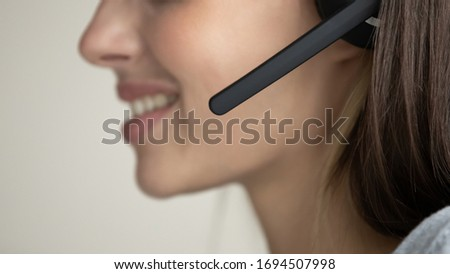 Close up of smiling female call center agent wearing wireless headset consult client, positive woman sales agent or operator talk speak on helpline, customer support service, assistance concept #1694507998