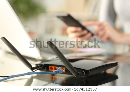 Close up of woman hands using multiple devices with broadband router on foreground Royalty-Free Stock Photo #1694512357