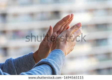 Woman hands applauding medical staff from their balcony. People in Spain clapping on balconies and windows in support of health workers, doctors and nurses during the Coronavirus pandemic #1694565115