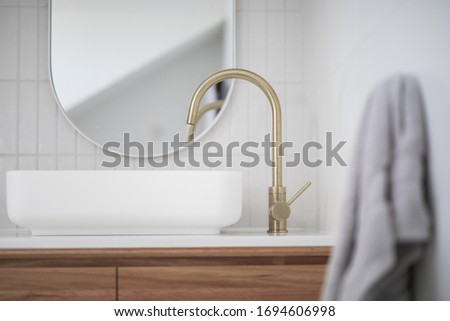 Brushed brass tap mixer on timber vanity with white basin bowl against white tiled wall in a new modern elegant bathroom lit by natural light from a nearby window modern interior house renovation new  Royalty-Free Stock Photo #1694606998