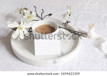 Spring wedding still life scene. Business, place card mockup, marble tray, cup of coffee. Vintage feminine styled photo. Floral composition with star magnolia blooming branches on white linen table.