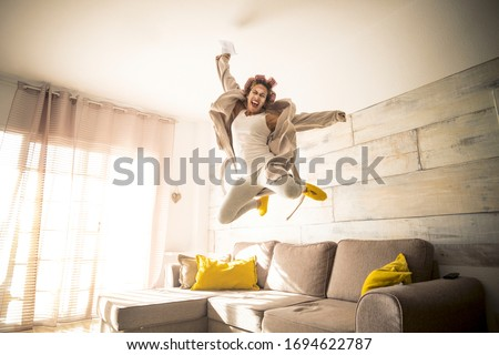 Concept of end quarantine coronavirus covid-19 lockdown stay home time - woman jump with joyful and happiness feeling emotions - concept of success and joy for people - high jump on couch at home #1694622787