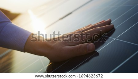 Close up of an young engineer hand is checking an operation of sun and cleanliness of photovoltaic solar panels on a sunset. Concept:renewable energy, technology,electricity,service, green,future Royalty-Free Stock Photo #1694623672