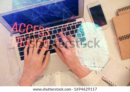 Double exposure of woman hands working on computer and fingerprint hologram drawing. Top View. Digital Security concept. #1694629117