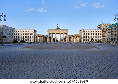 view on the famous Brandenburg gate on the Pariser square in Berlin city, parisian square without tourists and visitors - deserted, blue sky, small clouds Royalty-Free Stock Photo #1694629699