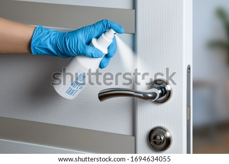 Door handle disinfection for the prevention of viral infection during the COVID-19 pandemic. White door. Door knob. Royalty-Free Stock Photo #1694634055
