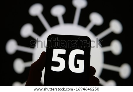 5G radiation in a shape of COVID-19. Concept. 5G letters on smartphone silhouette hold in a hand and coronavirus image on the background. Real photo, not a a montage. #1694646250