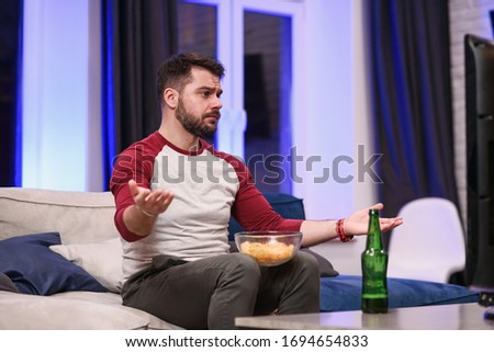 Good-looking modern positive 30-aged guy with well-groomed beard savoring chipps during emotional review of favourite football team's game on tv at home #1694654833