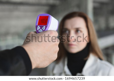 Operator check fever by digital thermometer visitor at information counter for scan and protect from coronavirus COVID-19. Royalty-Free Stock Photo #1694657239