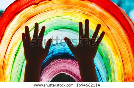 Close-up photo of child's hands touch painting rainbow on window. Family life background. Image of kids leisure at home, childcare, safety joy symbol. #1694662114