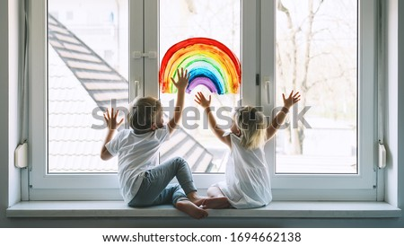 Little children on background of painting rainbow on window. Photo of kids leisure at home. Positive visual support during quarantine Pandemic Coronavirus Covid-19 at home. Family background Royalty-Free Stock Photo #1694662138