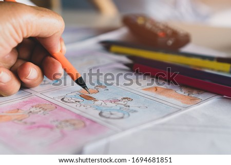 Video Pre-production for film movie storyboard concept : Hands drawing story board animation comic carton, design creative scene layout at studio. Behind process work before production films shot