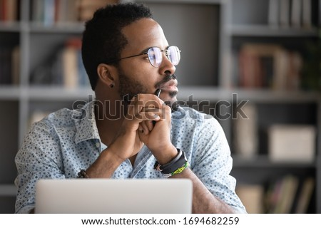 Pensive African American man in glasses distracted from computer work look in distance thinking or pondering, thoughtful biracial male lost in thoughts make plans visualizing, business vision concept #1694682259