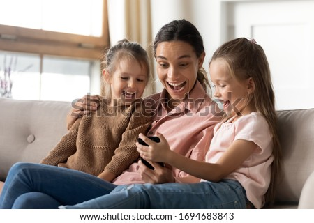 Excited young mixed race babysitter cuddling little children, looking at smartphone screen. Happy small girl showing funny cartoon photo on mobile phone to laughing mother and sister, resting at home.