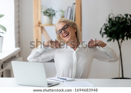 Happy 60 years old businesswoman with hands behind head relaxing in comfortable office chair during break. Smiling female employee with closed eyes resting after work done, leaning back. #1694683948