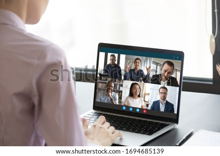 Computer monitor view over female shoulder during group video call with multi-ethnic international colleagues or friends. Distant communication and working use on-line app, internet connection concept #1694685139