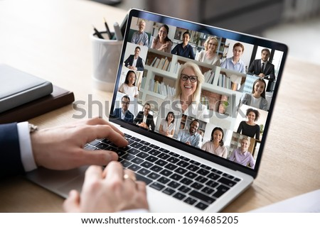 Businessman sit at desk use computer working on-line communicate distantly with colleagues by videoconferencing diverse people engaged in group video call, advertise worldwide virtual chat app concept Royalty-Free Stock Photo #1694685205